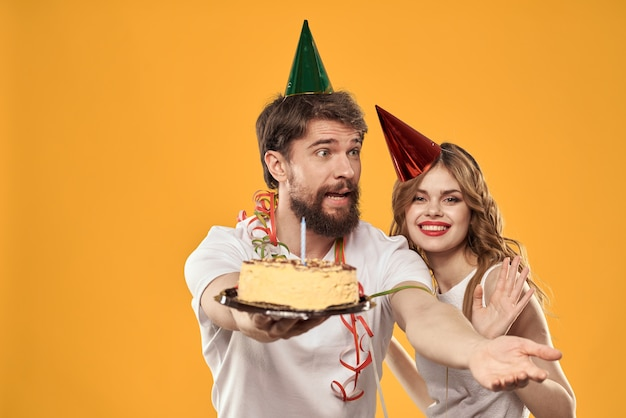 Gelukkig man en vrouw in een pet die een verjaardag vieren op een gele achtergrond met een cake in hun handen. hoge kwaliteit foto