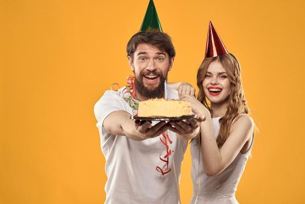 Gelukkig man en vrouw in een pet die een verjaardag vieren op een gele achtergrond met een cake in hun handen.