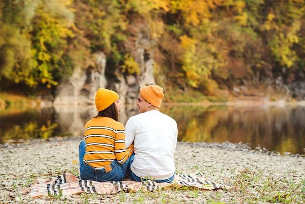 Gelukkig man en vrouw knuffelen en zoenen in de herfst.