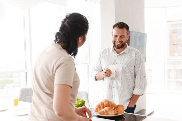 Gelukkig man en vrouw koken en ontbijten in huis, terwijl ze in lichte keuken staan