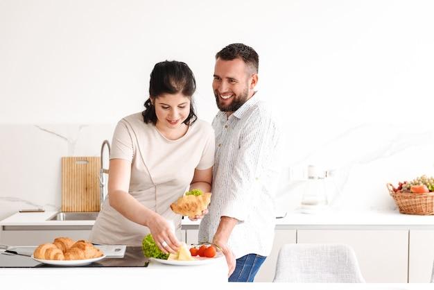 Gelukkig man en vrouw koken, en ontbijten in lichte keuken