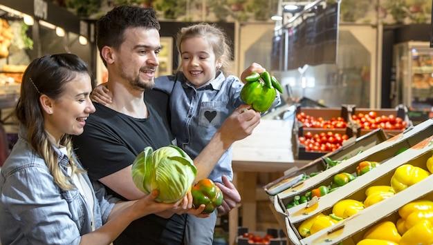Gelukkig man en vrouw met een kind kopen groenten. vrolijke familie van drie die paprika en greens in plantaardige afdeling van supermarkt of markt kiezen.