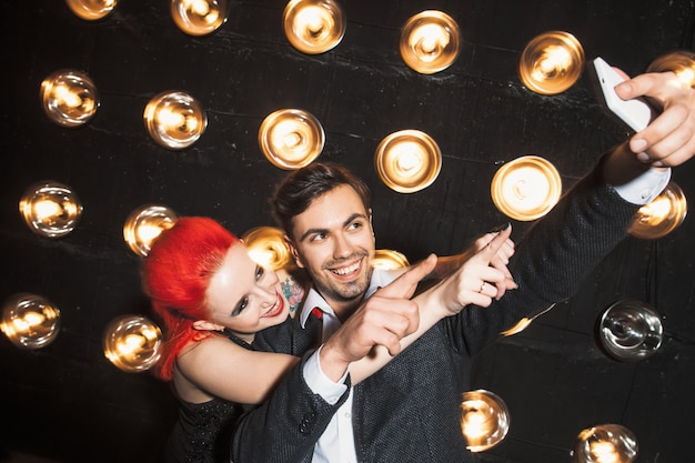 Gelukkig man en vrouw op nachtclub feest selfie maken