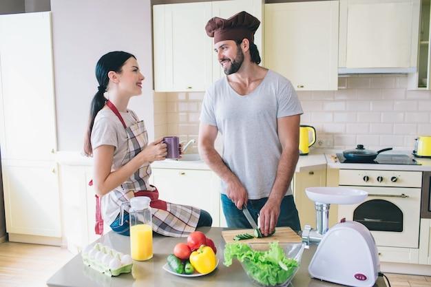 Gelukkig man en vrouw staan in de keuken en kijken naar elkaar. guy snijdt komkommer met mes.