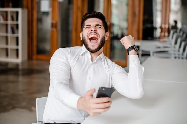 Gelukkig man enthousiast over overwinning op zijn telefoon op kantoor