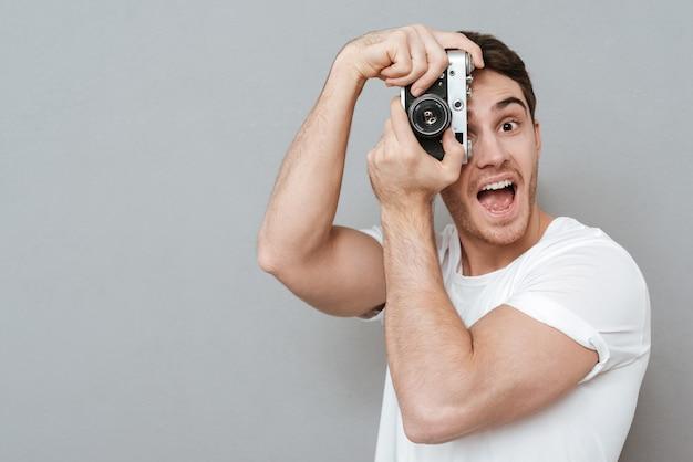 Gelukkig man foto maken op retro camera. geïsoleerde grijze muur
