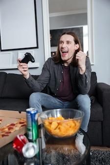 Gelukkig man gamer om thuis te zitten en spelletjes te spelen