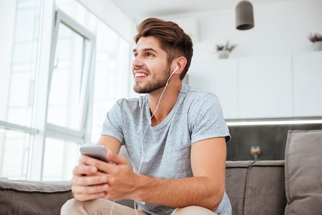 Gelukkig man gekleed in t-shirt luisteren naar muziek zittend op de bank en opzij kijken.