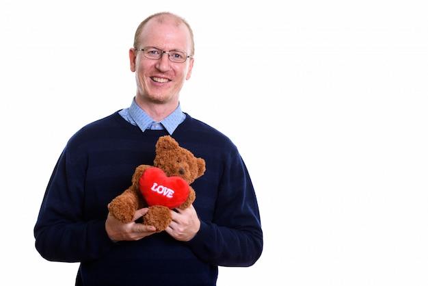 Gelukkig man glimlachend terwijl teddybeer met hart en liefde teken klaar voor valentijnsdag