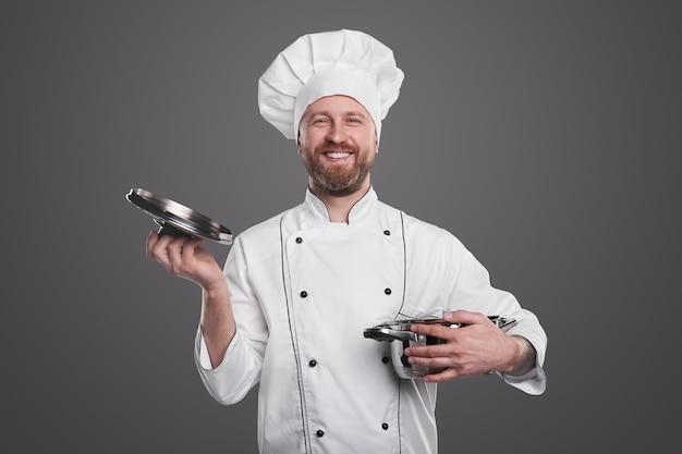 Gelukkig man in chef-kok uniforme pan openen en camera kijken tijdens het werken in restaurant tegen een grijze achtergrond