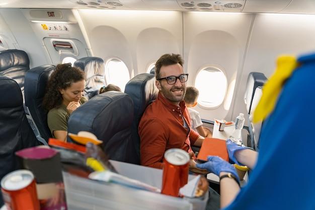Gelukkig man in glazen wachten op lunchbox aan boord van het vliegtuig