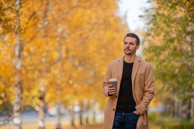 Gelukkig man in jas in herfst park loopt met koffie