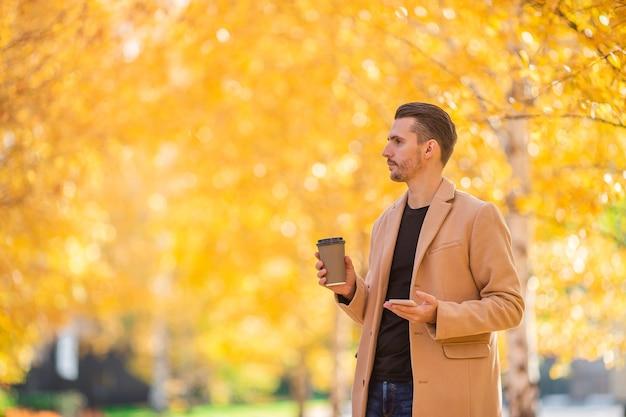 Gelukkig man in jas in herfst park met koffie