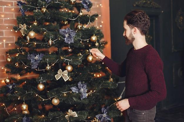 Gelukkig man in rode trui. kerel voor de open haard. mannetje op de achtergrond van de kerstboom.