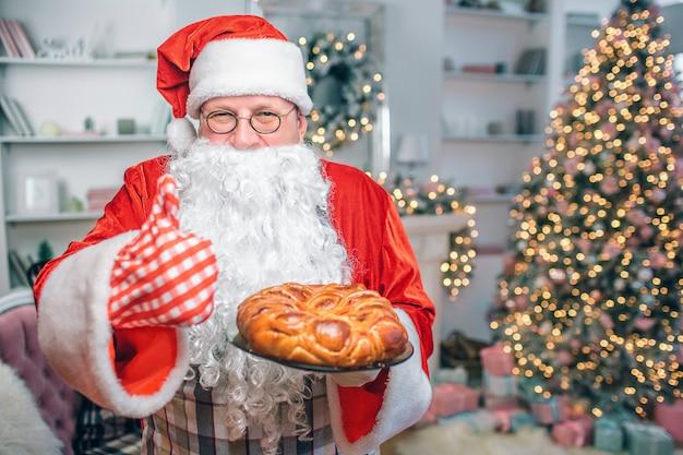 Gelukkig man in santa claus kleding houdt taart en toont grote duim omhoog. hij is alleen in de feestzaal.