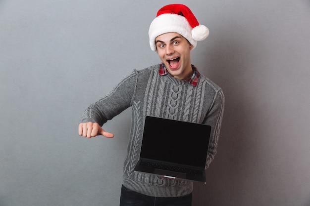 Gelukkig man in trui en kerstmuts met lege laptop computerscherm