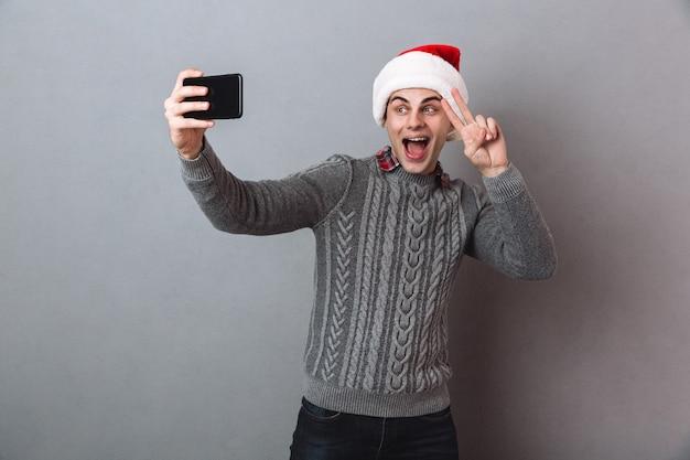 Gelukkig man in trui en kerstmuts selfie maken op smartphone en vredesgebaar tonen