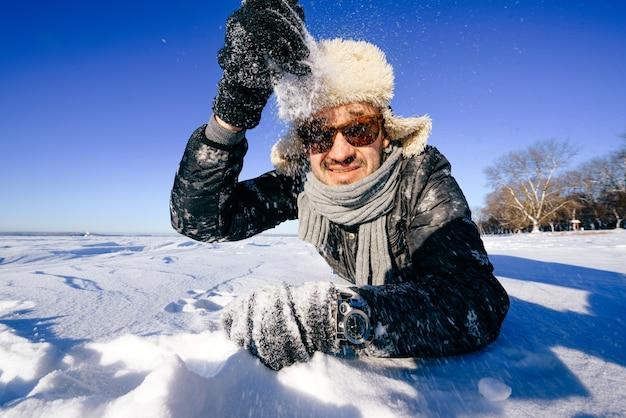 Gelukkig man in zonnebril buiten spelen met sneeuw