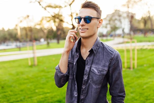 Gelukkig man in zonnebril, praten aan de telefoon, wandelen in het park