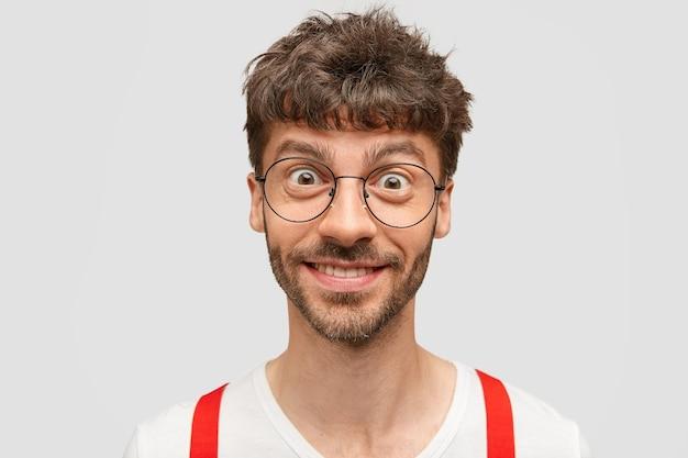 Gelukkig man kijkt met vrolijke en intrigerende uitdrukking, verheugt zich over zijn succes, draagt een ronde bril en witte kleren met rode bretels