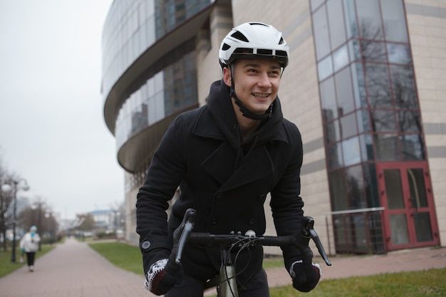 Gelukkig man lachen, genieten van fietsen in de stad in de herfst of winter