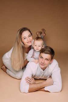 Gelukkig man liggend op de vloer met een schattige babyjongen op zijn rug en een liefhebbende vrouw aan zijn zijde.