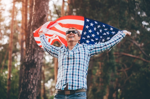 Gelukkig man loopt met usa vlag in park bij zonsondergang