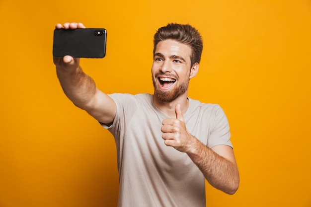 Gelukkig man maakt een selfie door smartphone met duimen omhoog.