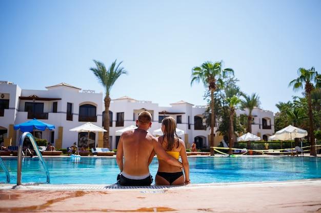 Gelukkig man man vreugde op vakantie, meisje zit naast in een gele zwembroek. groot zwembad, palmbomen, blauw water in het zwembad