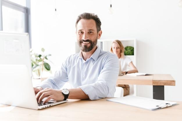 Gelukkig man manager die op laptopcomputer werkt