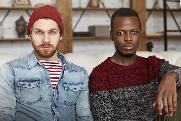 Gelukkig man met baard dragen hoed en jeans jasje zittend op de bank met zijn beste vriend