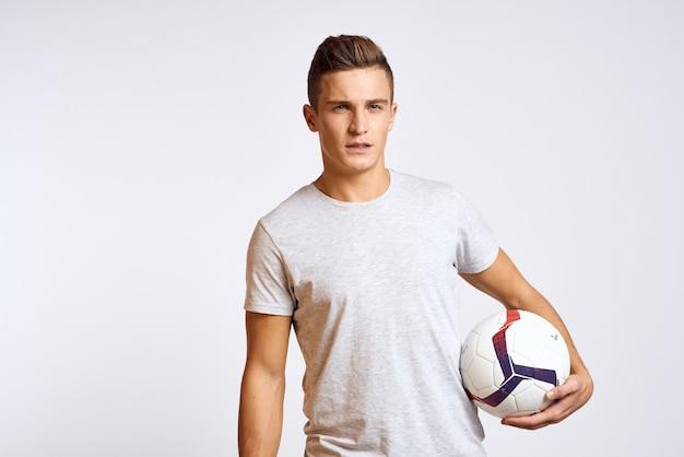 Gelukkig man met bal in de hand en in wit t-shirt op lichte achtergrond bijgesneden weergave.