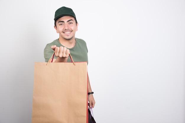 Gelukkig man met boodschappentassen tegen witte achtergrond.