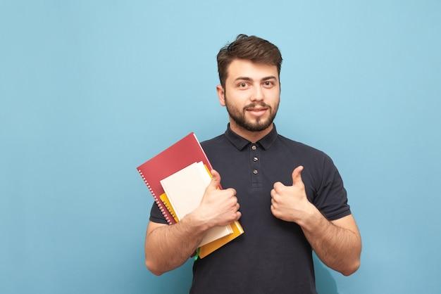 Gelukkig man met een baard en boeken en notitieboekjes in zijn hand toont een duim omhoog en glimlacht, geïsoleerd op blauw