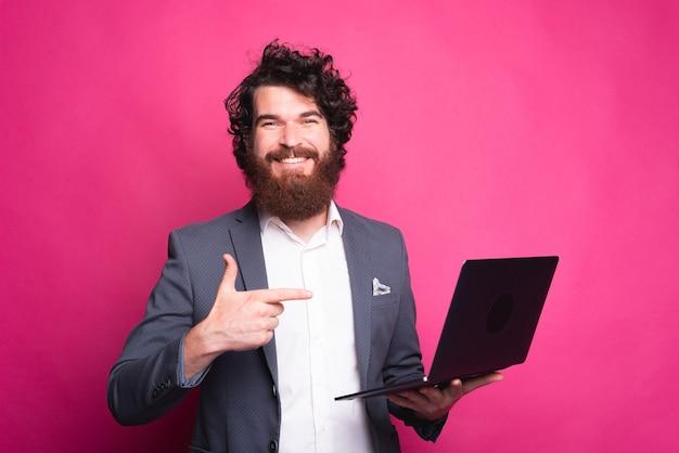 Gelukkig man met een computer en lacht naar de camera