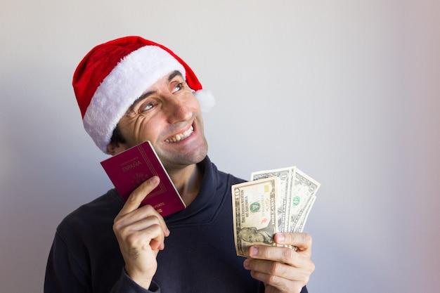 Gelukkig man met kerstmuts met paspoort en dollarbiljetten op witte achtergrond kerstvakantie