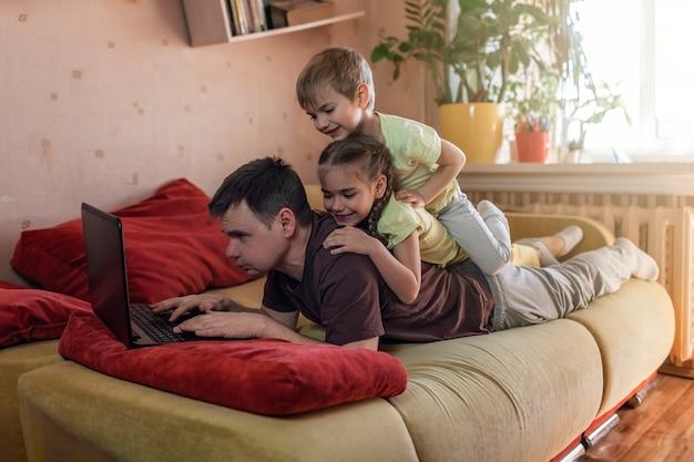 Gelukkig man met kinderen met behulp van laptop en oortelefoon tijdens zijn huis werken, leven in quarantaine