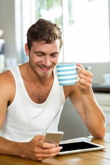 Gelukkig man met koffie tijdens het gebruik van mobiele telefoon thuis