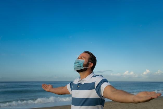 Gelukkig man met medische masker buiten tegen blauwe hemelachtergrond. persoon die in de zomer over zee geniet.