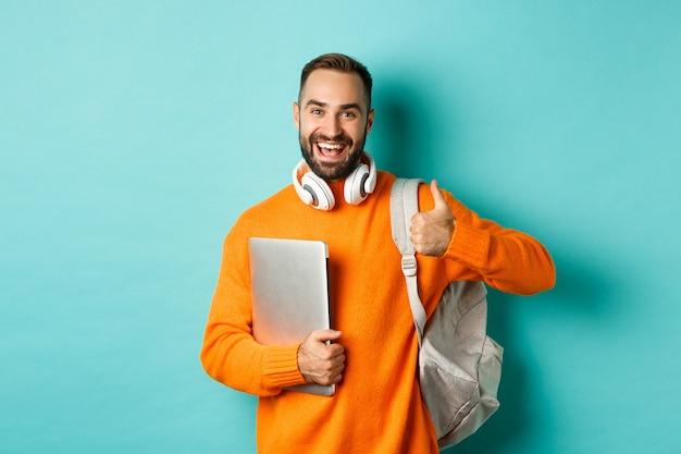 Gelukkig man met rugzak en koptelefoon, laptop vasthouden en glimlachen, duim-up in goedkeuring tonen, staande over turkooizen achtergrond.