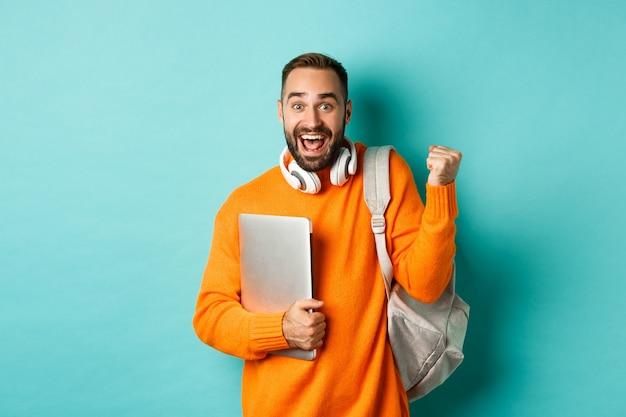 Gelukkig man met rugzak en koptelefoon, laptop vasthouden en glimlachen, juichen om te winnen, triomfen