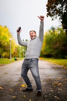 Gelukkig man met smartphone en oortelefoons in het park