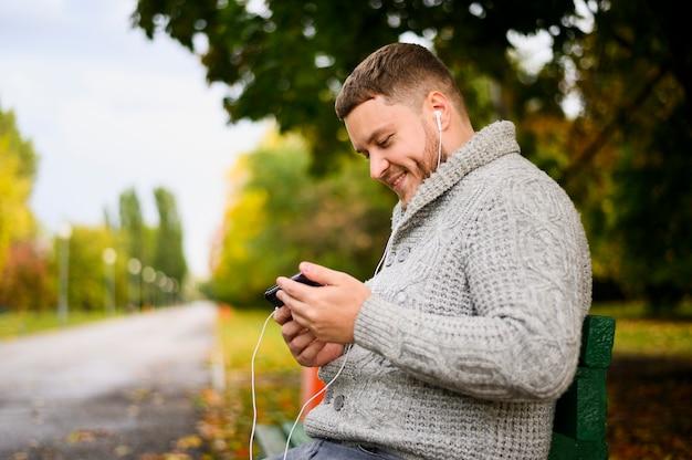 Gelukkig man met smartphone en oortelefoons op een bankje