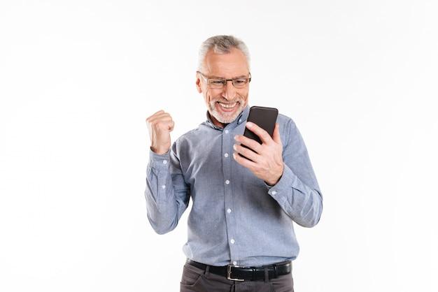 Gelukkig man met smartphone en winnaar gebaar maken