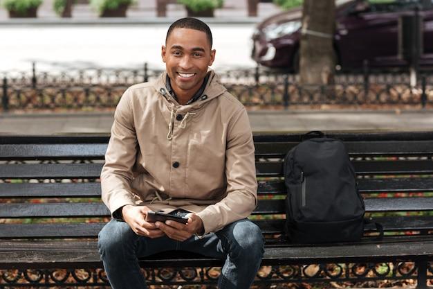 Gelukkig man met tablet zittend op een houten bankje in de buurt van rugzak en chatten