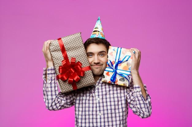 Gelukkig man met verjaardagsgiften in dozen over paarse muur.