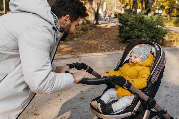 Gelukkig man met zijn kind buiten in de wandelwagen