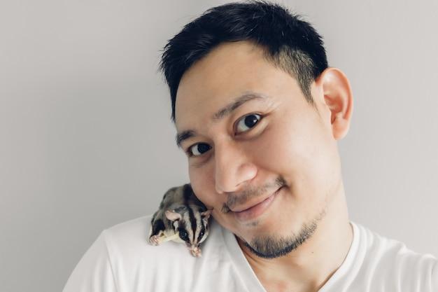 Gelukkig man neemt selfie van zichzelf en zijn huisdier sugar glider.