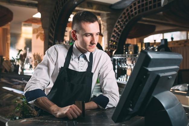 Gelukkig man of ober in schort aan balie met kassa werken bij bar of coffeeshop