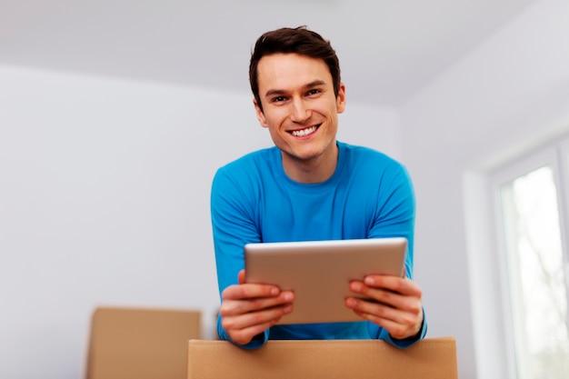 Gelukkig man organiseren verhuizing in zijn nieuwe appartement